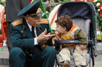 An Armenian war veteran speaks with a young child during Victory Day celebrations in Yerevan (Karen Minasyan/Getty Images).